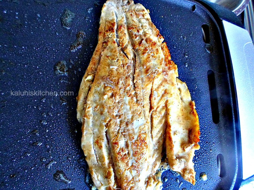 frying the fish, about 5 minutes on each side until the flesh turns white_do not remove the clinging pieces of garlic_Kaluhis Kitchen