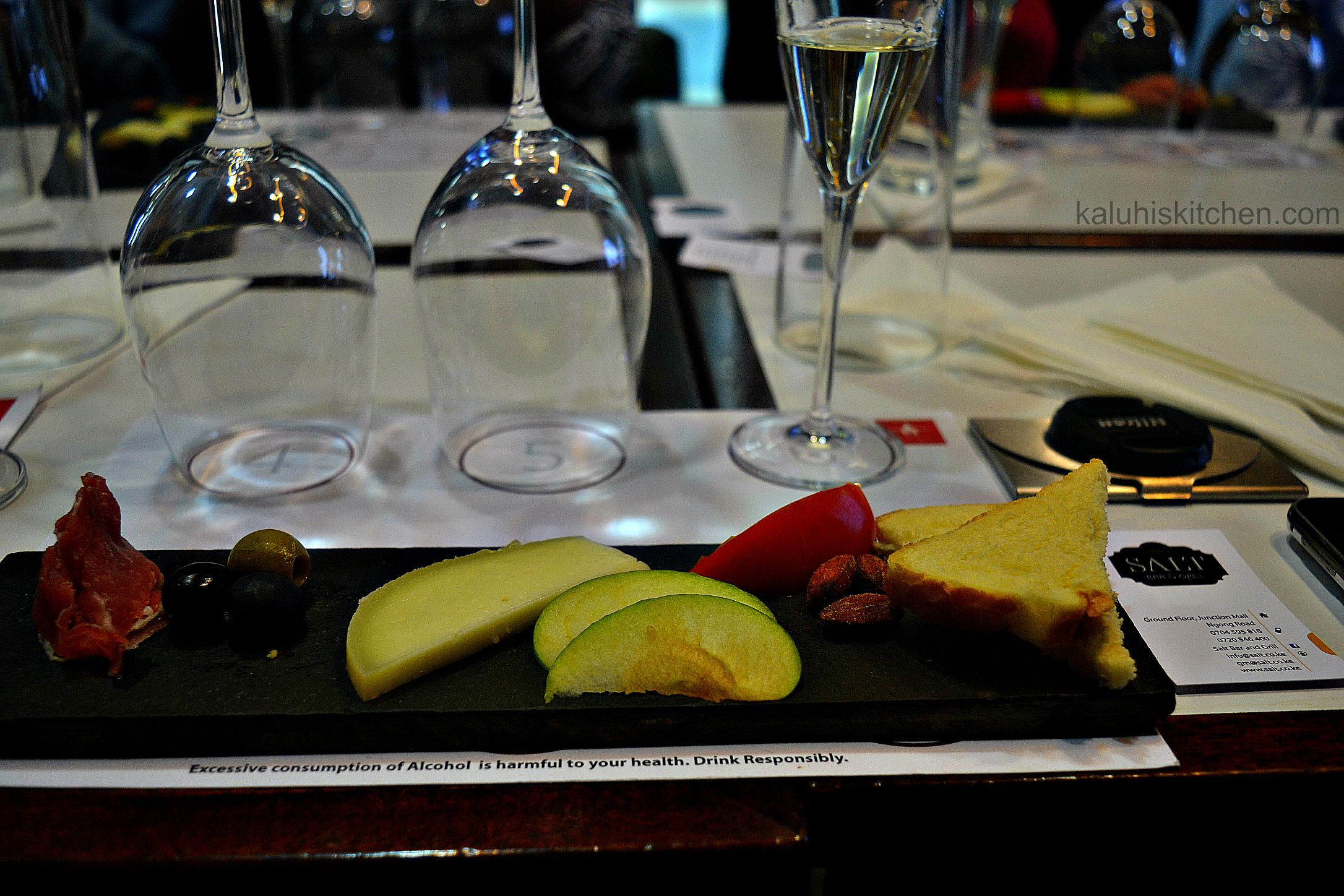 goat cheese, toast, tomato, almonds and olives are some of the food that accopmanies the cava brut as served by salt bar and grill_kaluhiskitchen.com