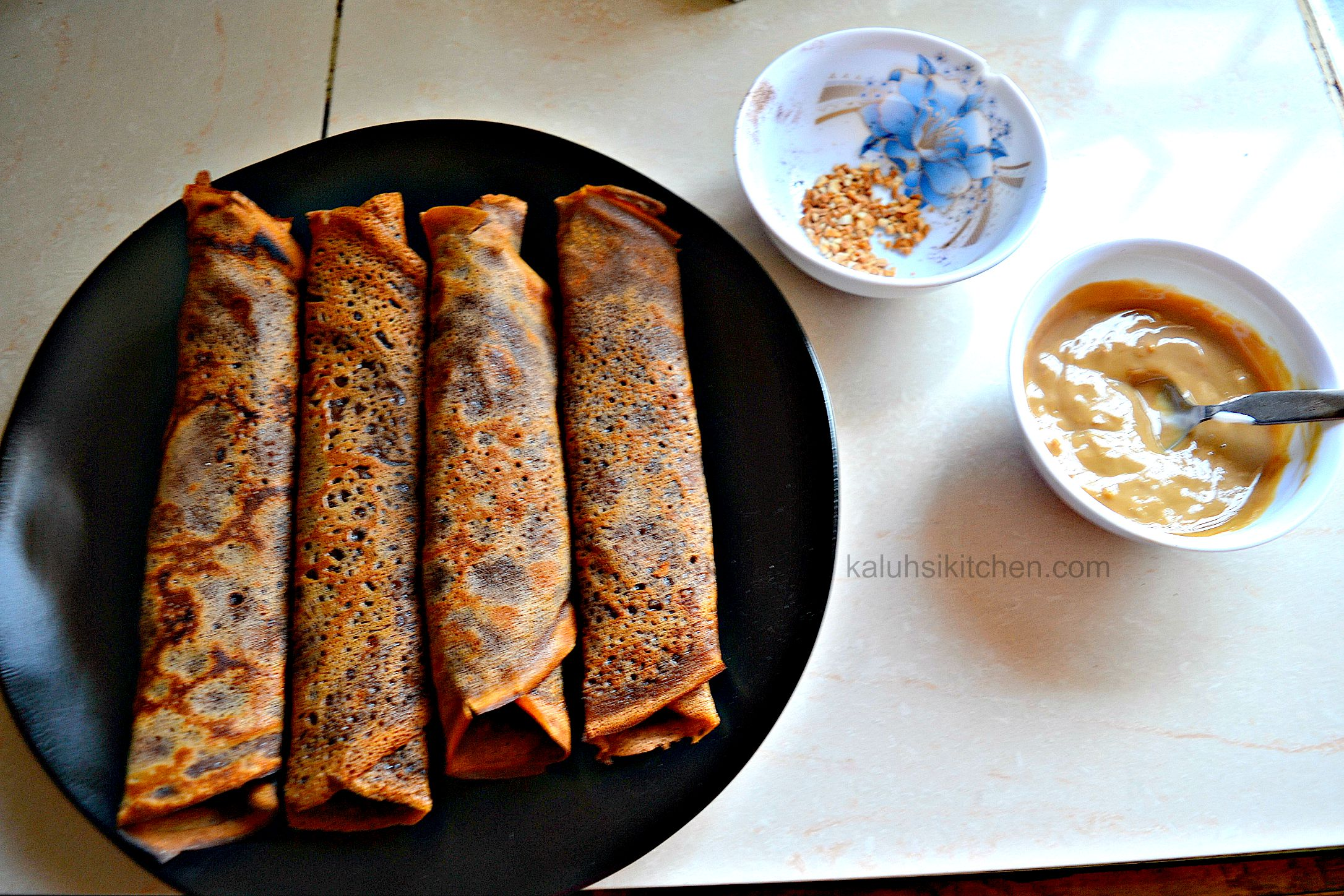 rolled up coffee crepes ready for serving and ganishing with coffee cream and nuts_crepe recipe by kaluhiskitchen.com