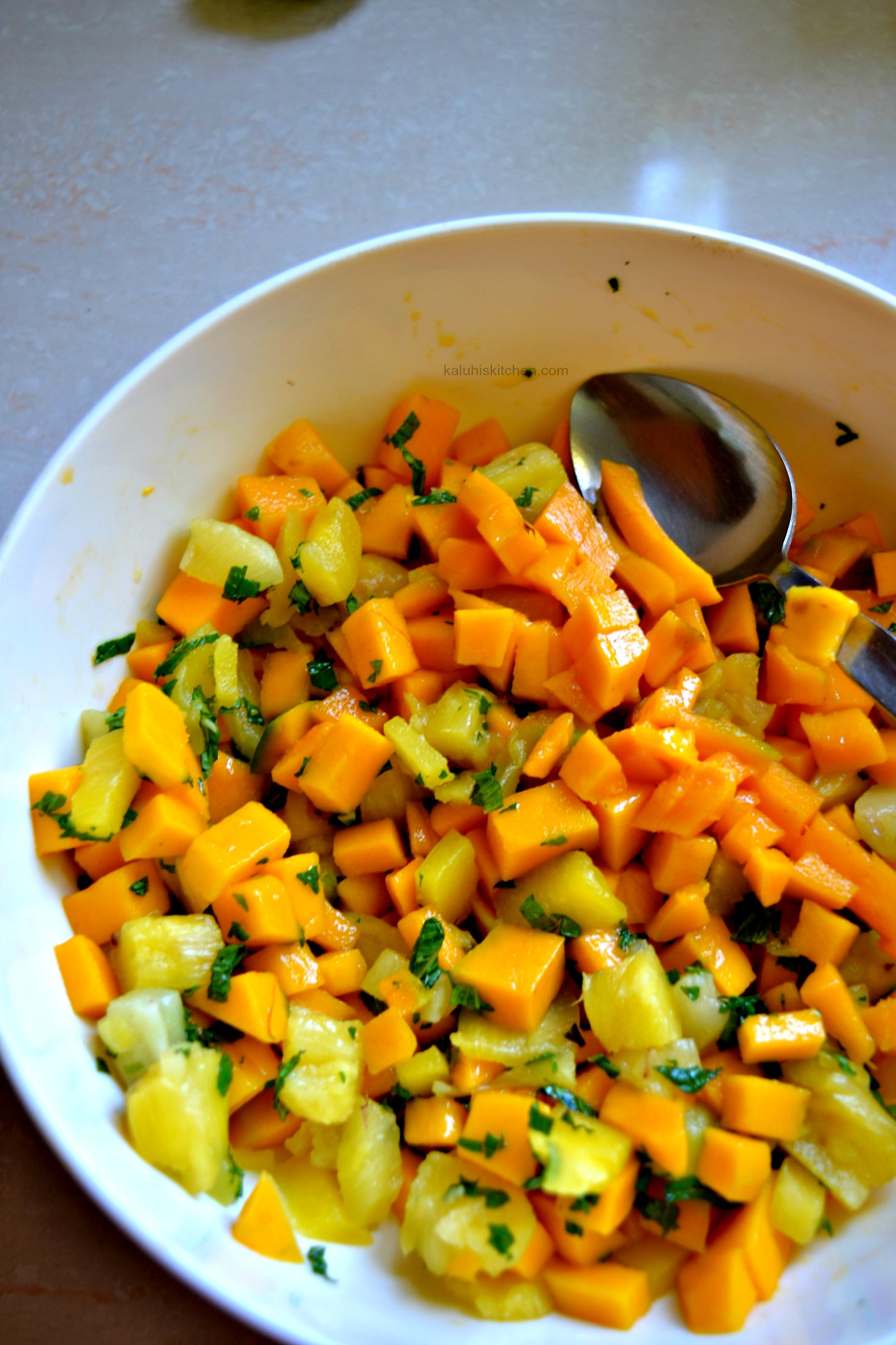 mix all the fruits of your mango mint salad together amd allow it to rest for a few minutes so that all the flavors mix in_kaluhiskitchen.ocm